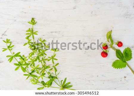 Strawberry with grass on old wooden table