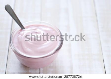 strawberry yogurt on wooden white background. strawberry yoghurt. pink yogurt.