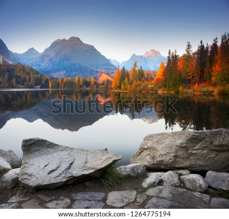 Strbske Pleso is the second largest lake on the Slovak side of the High Tatras. The ski resort, hotels under the mountain tops are very beautiful and famous/ On the shore are red boats #1264775194