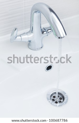 Stream and drops of pure water in a sink