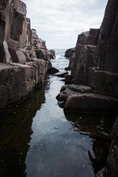 Stream flowing into rocky Lake Superior, rocky shoreline, Grand Marais