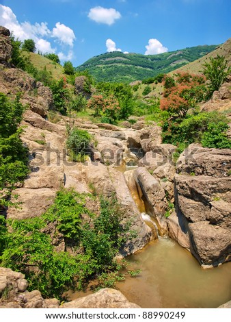 stream flowing over rocks in the background of the mountains. natural composition