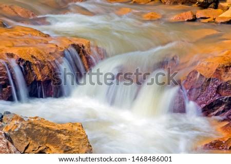 stream flows through gold-like stones