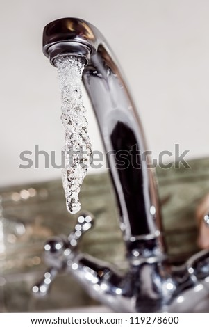Stream of cold water flows from the metal tap