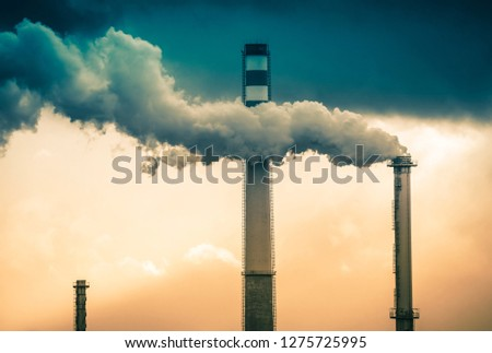 Stream of dark smoke from the chimney of factory in the industrial district