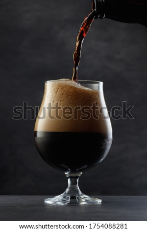 Stream pouring dark beer from the bottle into a beer glass.     Jet of the dark porter pours and whips the thick foam in a half-pint glass against the background of a blurred gray granite wall Сток-фото ©