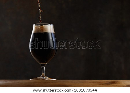 Stream pouring dark beer from the bottle into a beer glass. Jet of the dark porter pours and whips the thick foam in a pint glass against the background of a blurred brown granite wall on wooden table Stock photo ©