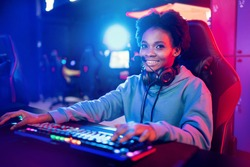 Streamer african young woman rejoices in victory professional gamer playing online games computer with headphones, neon color.