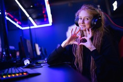 Streamer beautiful girl shows heart sign with hands professional gamer playing online games computer, neon color.