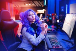 Streamer beautiful woman shows heart sign with hands professional gamer playing online video games computer, neon color.