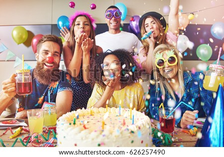 Streamers surrounding group of cheerful friends celebrating a party with large cake and drinks on table in foreground Foto stock ©