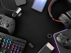 streaming games concept, top view a gaming gear, mouse, Webcams, keyboard, joystick, headset and mouse pad on black table background.