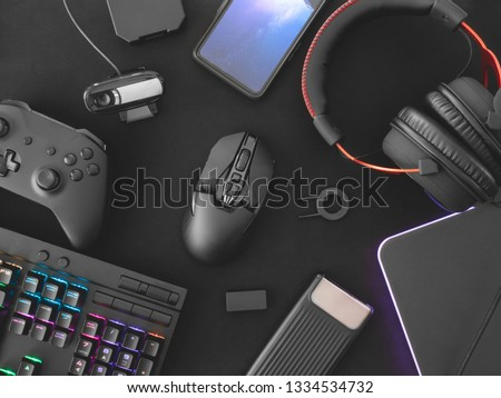 streaming games concept, top view a gaming gear, mouse, Webcams, keyboard, joystick, headset and mouse pad on black table background. #1334534732