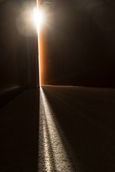 Streaming light coming through a crack in a slightly open door at the end of a dark hallway representing hope and opportunity just beyond the door.