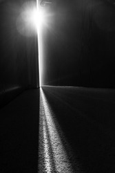 Streaming light coming through a crack in a slightly open door at the end of a dark hallway representing hope and opportunity just beyond the door in black and white.