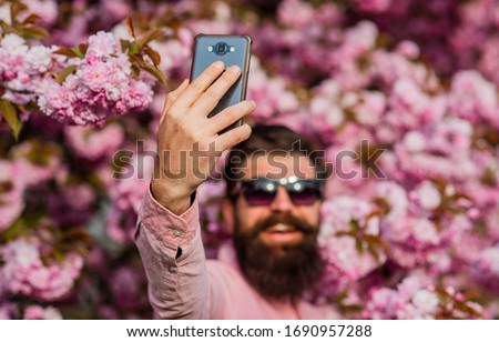 Streaming online video call. Mobile internet. Tourist capture happy moment for blog. Mobile phone blogger. Blog online content. Personal blog. Selfie with sakura. Man taking selfie photo smartphone.