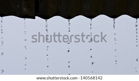 Streams of rain water pour off a corrugated roof, grey roof, green background selective focus