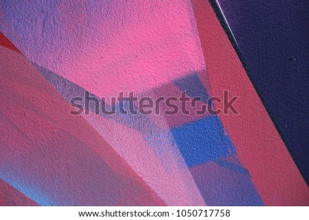 Street art. Colorful graffiti on the wall. Fragment for background. Detail of a graffiti. Abstract graffiti on the wall. Colorful (red, blue, pink and black) wall as background
