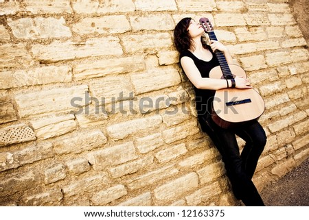 Street artist holding guitar on the wall