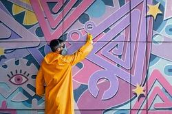 Street artist painting colorful graffiti on wall. Modern urban art concept