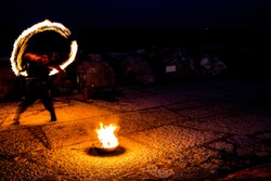 Street artist with a burning stick during his dangerous fire show