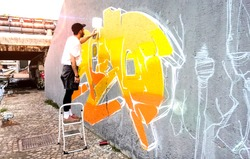 Street artist working on colored graffiti at public wall - Modern art concept of urban guy painting live murales with yellow and orange aerosol color spray - Bright sunflare filter - Focus on artwork
