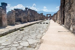 Street at ruins of ancient city Pompeii, destroyed by volcanic eruption of Vesuvio mountain, Italy