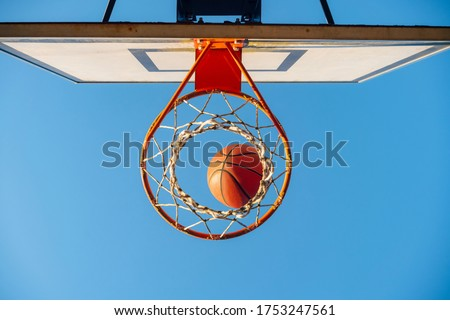 Street basketball ball falling into the hoop. Urban youth game. Close up of orange ball above the hoop net. Concept of success, scoring points and winning Stock photo ©