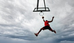 Street basketball player making a powerful slam dunk on the court - Athletic male training outdoor on a cloudy sky background - Sport and competition concept