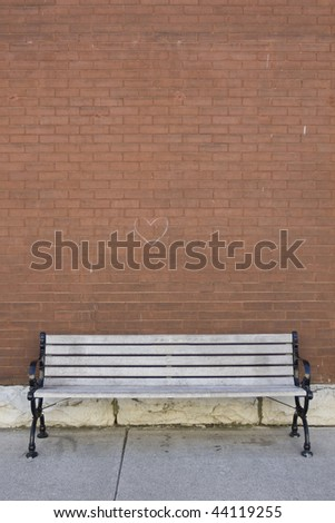 street bench in front of red brick wall