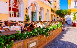 Street cafe and restaurant table and chair on Capri Island town in Italy at Naples. Landscape with Terrace Cafeteria at Italian coast. Anacapri in Europe. Summer. Amalfi scenery. Amalfina coastline.