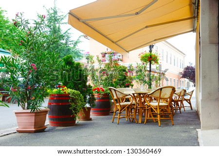 Street cafe under canopy. Red flowers in octaves and wood barrels. #130360469