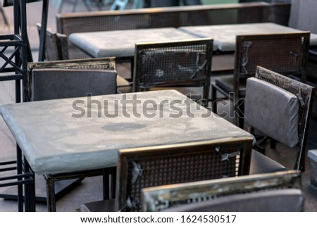 street cafe with a gray painted iron table and black iron chairs with soft pillows in a rough urban style, nobody close up.