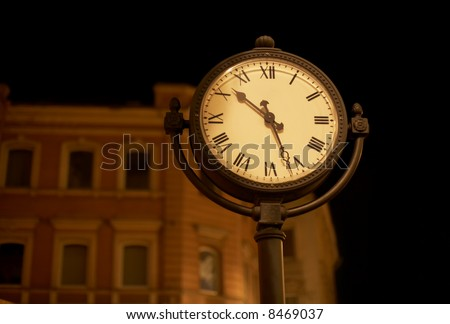 Street clock at night time against blurry building.