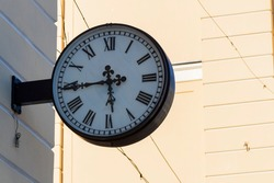 Street clock on the wall of the house. Classic dial with Roman numerals.