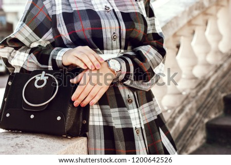 Street close up photo of trendy fashion details of elegant autumn outfit: stylish black bag, silver wrist watch, woman wearing checked dress. Copy, empty space for text