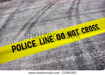 Street crime scene with police line do not cross yellow warning tape above road with tire tracks