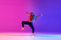 Street dance style. Young beautiful female hip-hop dancer dancing isolated on neon background. Sport achievement, spirit of expression. Concept of dance, youth, hobby, dynamics, movement, action, ad