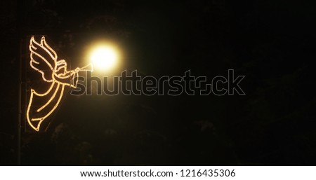 street decoration of light bulbs in the form of an angel with a mountain glows in the dark next to the street lamp #1216435306