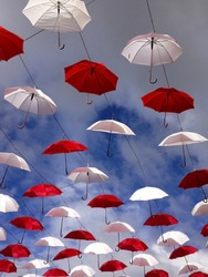 Street decoration of white and red umbrellas in a row floating in the air