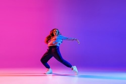 Street dynamics. Young beautiful hip-hop girl dancing isolated on neon studio background. Sport achievement, spirit of expression. Concept of dance, youth, hobby, dynamics, movement, action, ad