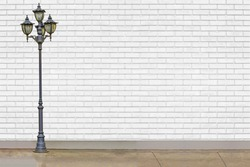 street electric lamp post at white brick wall