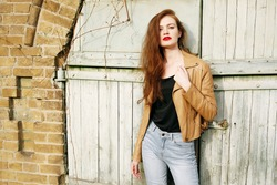 Street fashion concept - closeup portrait of a pretty hipster girl. Wearing brown leather jacket and high waisted jeans. Beautiful autumn woman with red libs and curly hair. Artsy bohemian style.