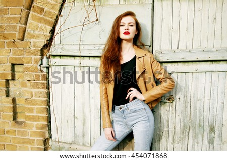 Street fashion concept - closeup portrait of a pretty hipster girl. Wearing brown leather jacket and high waisted jeans. Beautiful autumn woman with red libs and curly hair. Artsy bohemian style.  #454071868