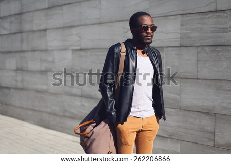 Street fashion concept - stylish handsome african man standing in the city against a gray textured wall