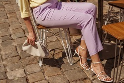 Street fashion details of elegant woman`s summer outfit: lilac trousers, white strap sandals, leather pouch handbag