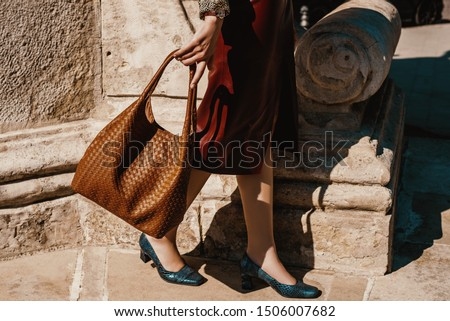 Street fashion details: woman wearing leather skirt, blue snakeskin, python print square toe shoes, holding brown wicker pattern hobo bag, handbag. Copy, empty space for text