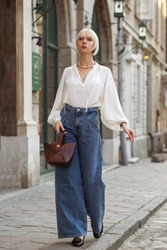 Street fashion full-length portrait of elegant  woman wearing trendy white blouse, stylish high waist wide jeans, holding brown croco leather textured bag. Model walking in street of European city