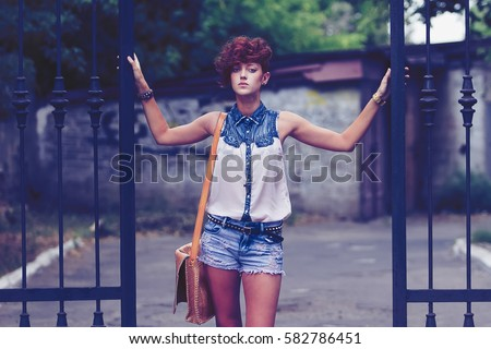 Street fashion model girl posing outdoor in summer.Cool skinny female model with modern hair style.Fashionable young white woman outside.Beautiful hairstyle for youth.Trendy haircut for spring season #582786451