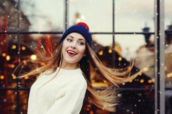 Street fashion portrait of smiling beautiful young woman playing with her long hair. Lady wearing classic winter knitted clothes. Model looking aside. Festive  garland lights. Snowfall effect. Toned